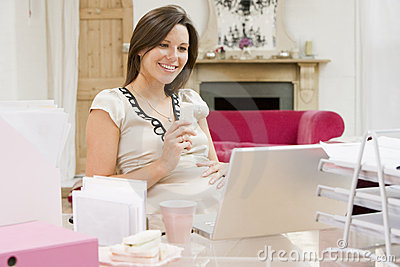 Pregnant woman in home office with laptop eating
