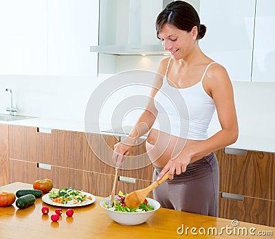 Pregnant woman at kitchen preparing salad