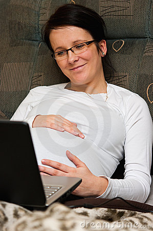Pregnant woman with laptop in bed