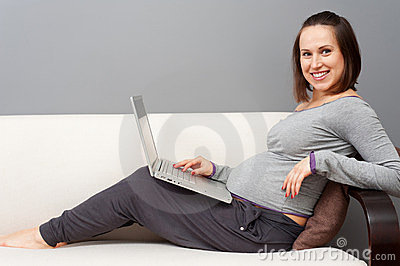 Pregnant woman with laptop at home