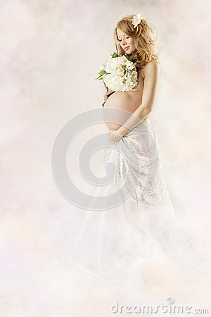 Pregnant woman looking at flowers in white dress.