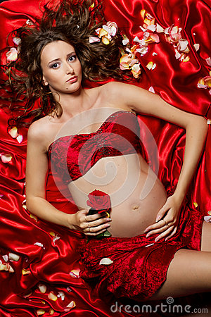 Pregnant woman lying on red silk with rose petals