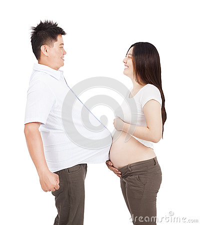 Pregnant woman and man with football under shirt