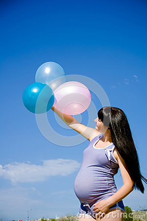 Pregnant woman on a meadow with blue sky