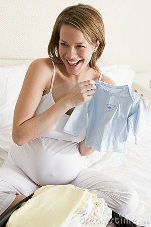 Pregnant woman packing baby clothing in suitcase