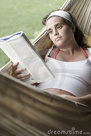 Pregnant woman reading a magazine on a hammock