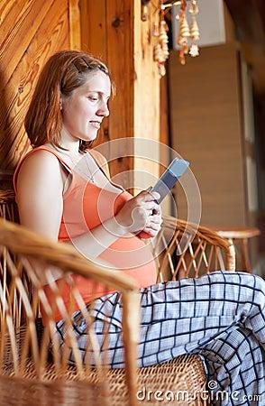 Pregnant woman reads e-book