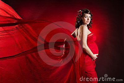 Pregnant woman in red waving dress