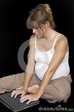 Pregnant woman sitting down using laptop