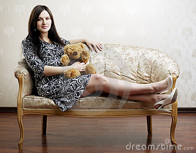 Pregnant woman sitting on a vintage couch