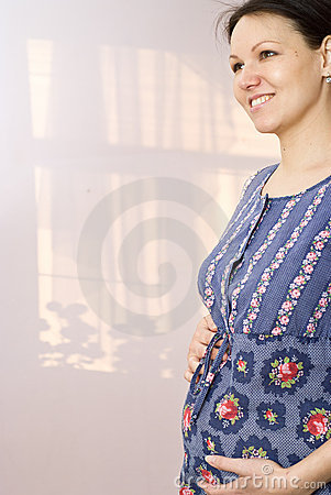 Pregnant woman standing and holding on to stomach