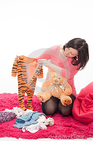 Pregnant woman with teddy bear and children s clothes