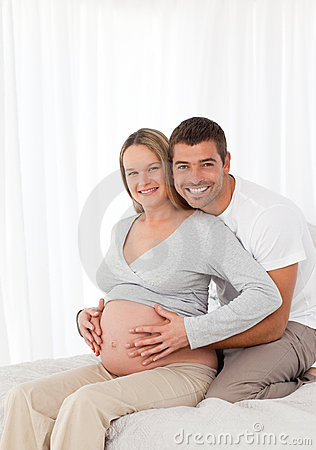 Pregnant woman touching her belly with her husband