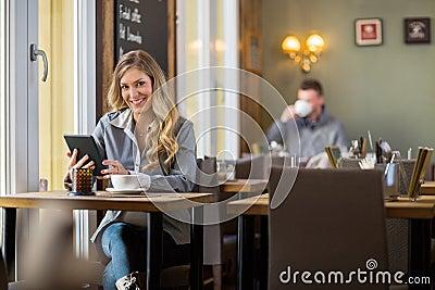 Pregnant Woman Using Digital Tablet In Coffeeshop