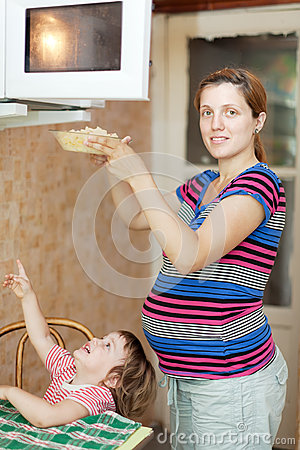 Pregnant woman warms up food