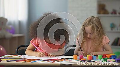 Première éducation, deux enfants féminins multi-ethniques dessinant avec les crayons colorés banque de vidéos