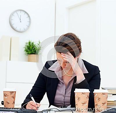 Preocupe a la mujer de negocios envejecida media mientras que en el trabajo