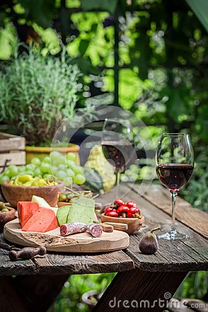 Free Preparation For Dinner With Cheese, Red Wine In The Garden Royalty Free Stock Photography - 109338637