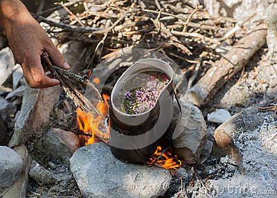 Preparing tea on campfire.