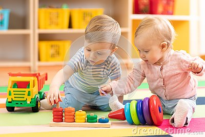 Preschool boy and girl playing on floor with educational toys. Children at home or daycare. Stock Photo