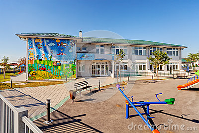 Preschool building exterior with playground on a sunny day.