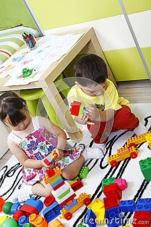 Preschool children build castles with plastic cubes
