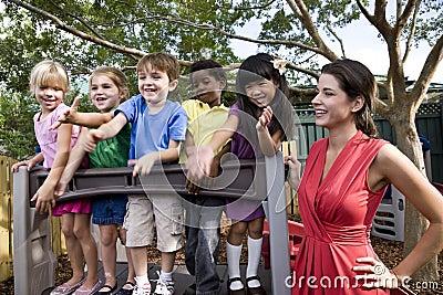 Preschool children on playground with teacher