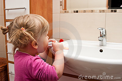 Preschool girl brushing teeth