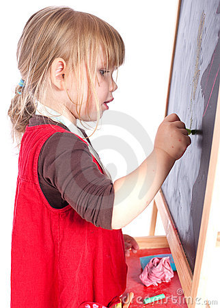 Preschool girl drawing on blackboard