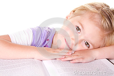 Preschool girl laying on large book