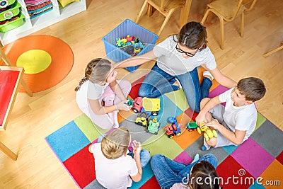 Preschool teacher talking to group of children sitting on a floor at kindergarten Stock Photo