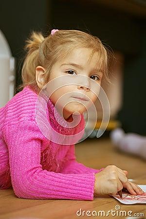 Preschooler draws a pencil on paper
