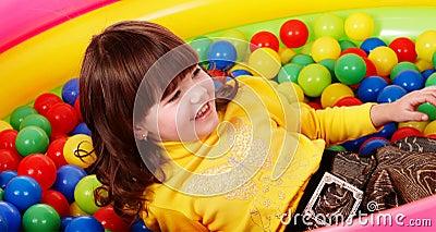 Preschooler girl with ball in play room.