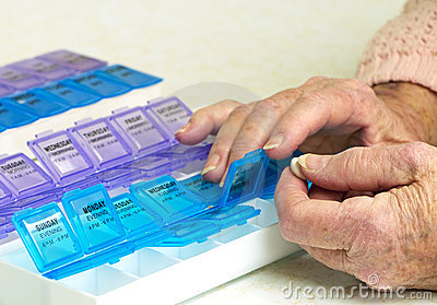 Prescription Drugs In Organizer With Elderly Hands