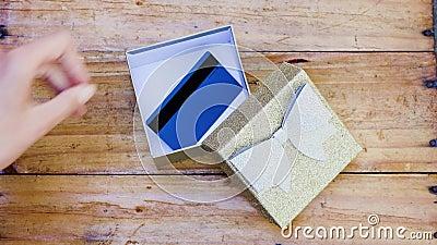 Presenta y sorpresas, colocando a mano la tarjeta de pago o la tarjeta de regalo dentro de la caja de regalo de brillo almacen de video