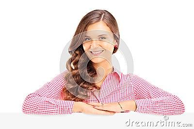 Presentación femenina joven sonriente detrás de un panel en blanco