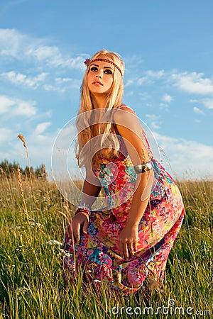 Presentación rubia hermosa en prado contra el cielo azul