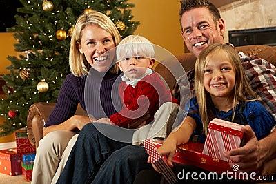 Presente di apertura della famiglia davanti all albero di Natale
