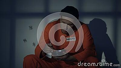 Preso masculino que come las gachas de avena en la célula, nutrición escasa, condiciones pobres metrajes