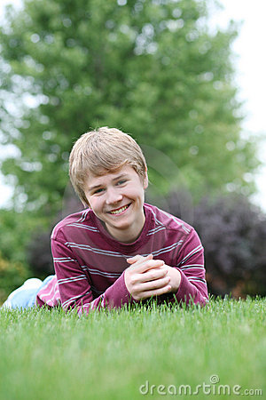 Preteen boy smiling in grass
