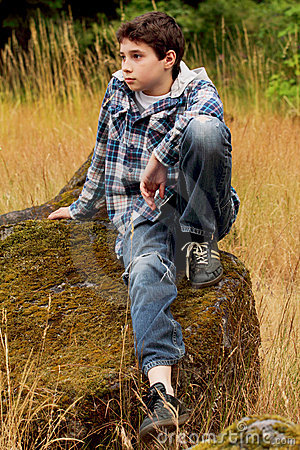 Preteen Country Boy Sitting on a Rock