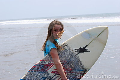Preteen girl carrying a surfboard to the ocean