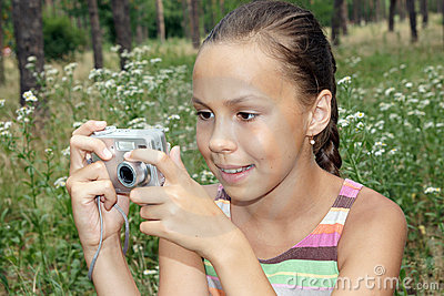 Preteen girl making pictures with digital camera on green grass ...