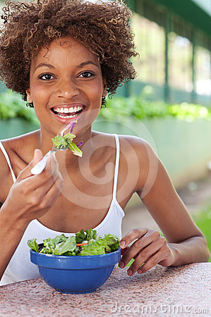 Pretty African American woman eating a salad