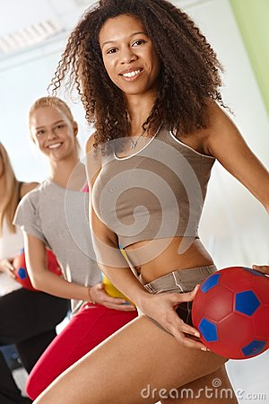 Pretty afro woman exercising with ball
