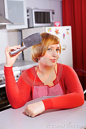 Pretty artful housewife with knife at kitchen