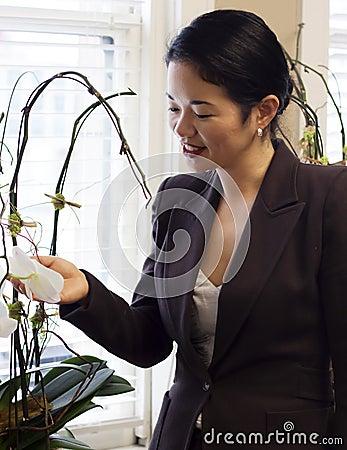 Pretty asian businesswoman admiring office plants