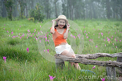 Pretty Asian woman sitting on flower field.