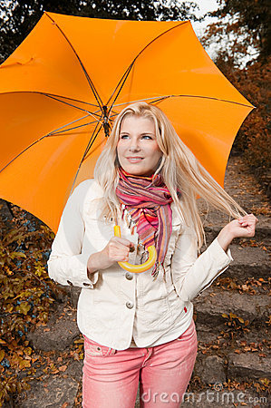 Pretty autumn woman in a forest with umbrella