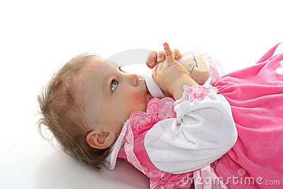 Pretty baby girl is drinking milk